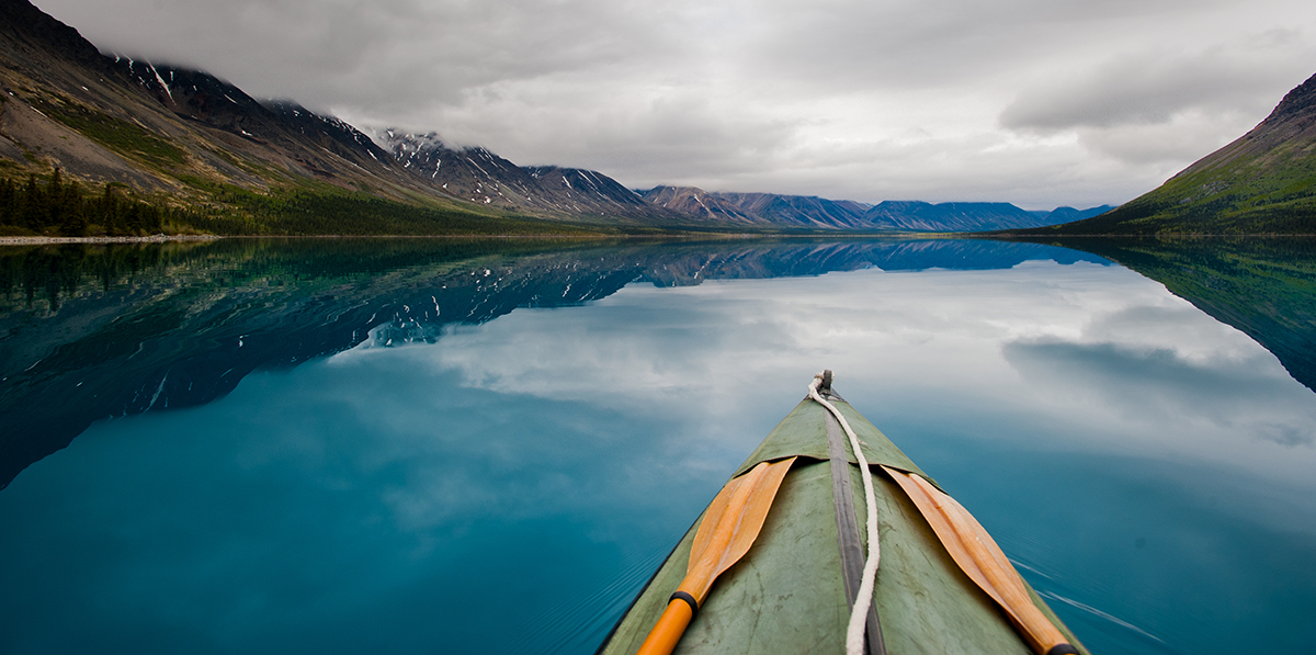 looking over the bow of a kayak across a blue lake toward cloud-covered mountains