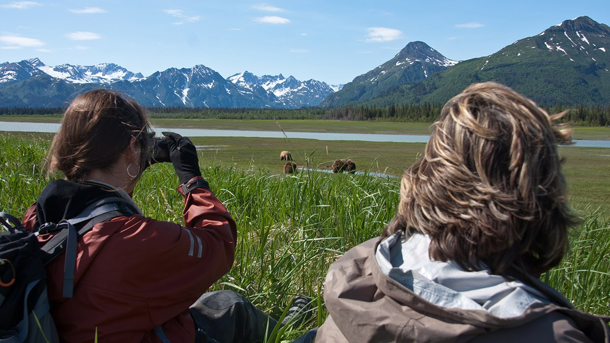 Photo of two women watching three brown bears through binoculars with a river and tall mountains in the background.