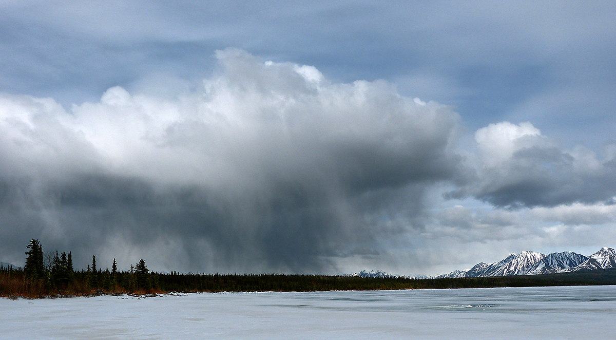 Photo looking across a frozen lake at a storm cloud which is raining in a small area.