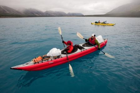 Red double hole kayak on turquoise-colored lake with foggy mountains in the distance. Warmly dressed young person paddling with double bladed paddle in front, wamly dressed adult paddling in rear. Yellow kayak in distance.