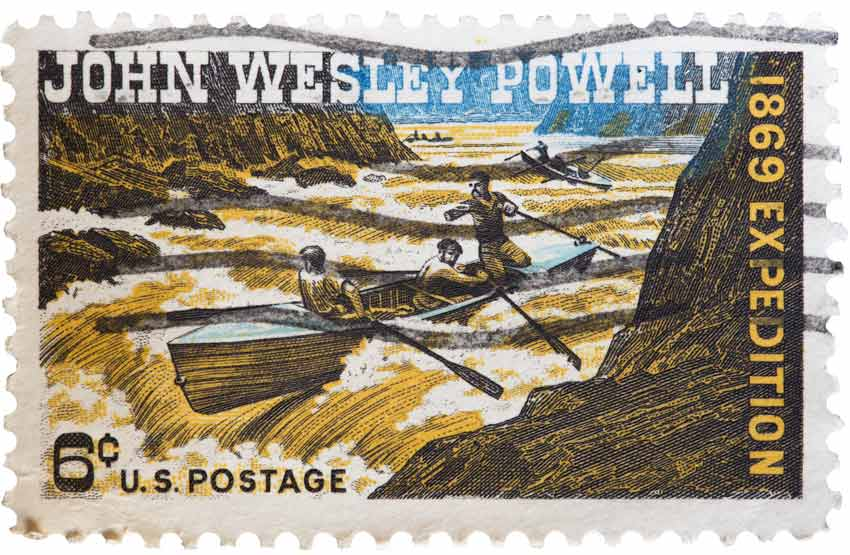 A postage stamp showing John Wesley Powell facing the rapids of a river.