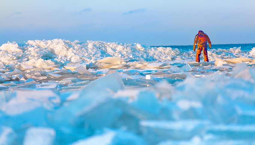 A researcher walks along an icy beach