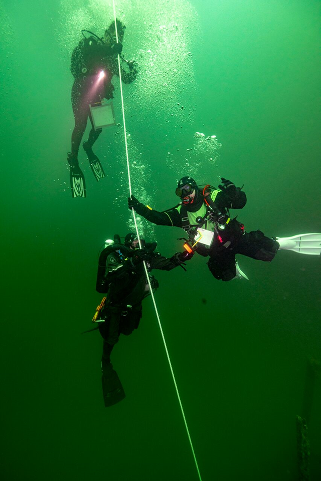 A group of 3 divers use their hands to follow a fixed rope down, releasing clouds of bubbles as they descend.