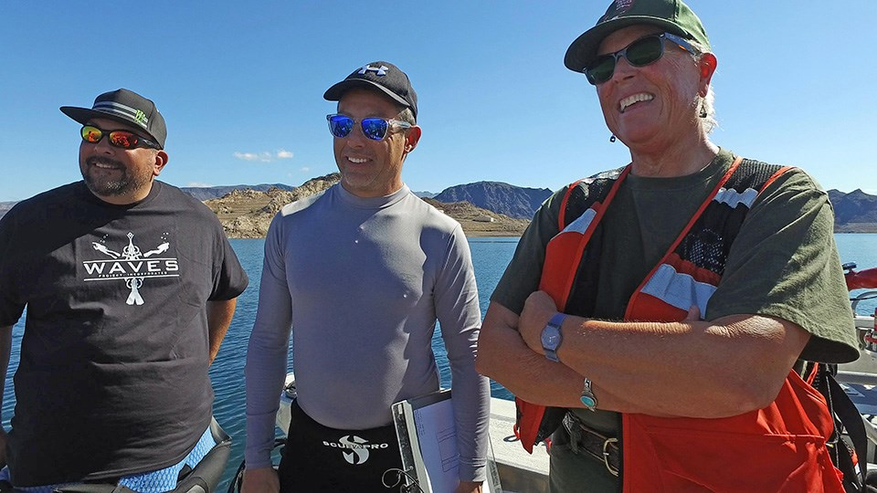 3 participants pose for a photo during meeting on the lake.