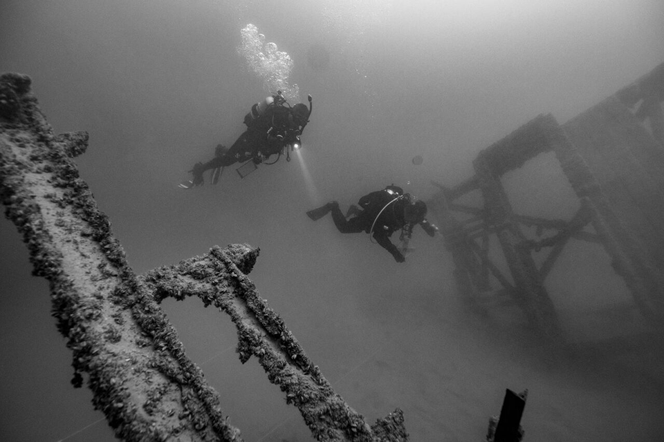 Two divers release cloud of air bubbles as they explore underwater structures in a black and white photo.