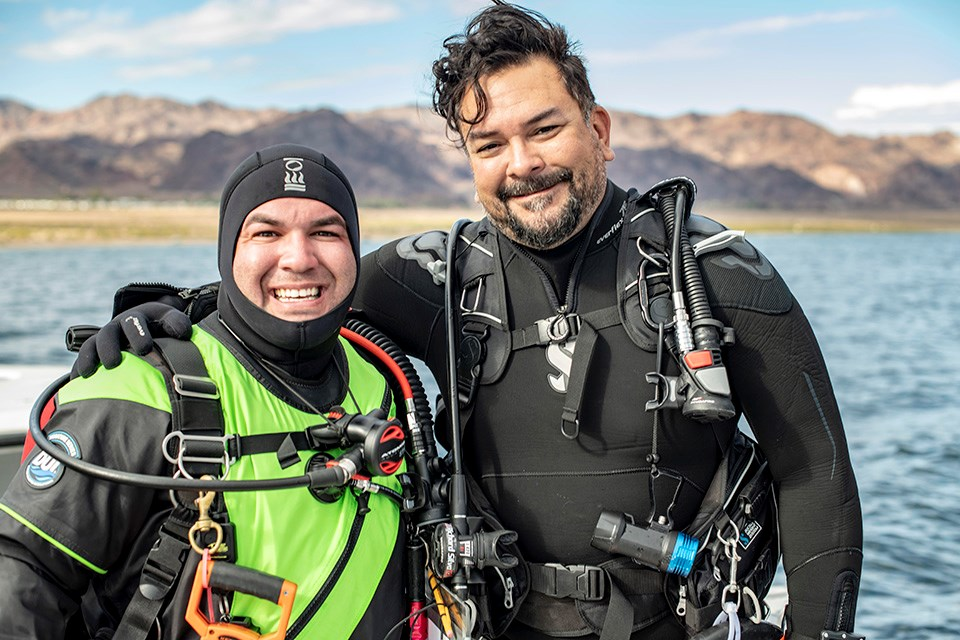 Two divers in wetsuits pose with all their gear prior to dive.