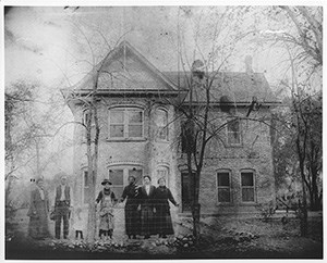 A group of settlers in front of a Victorian-style home.