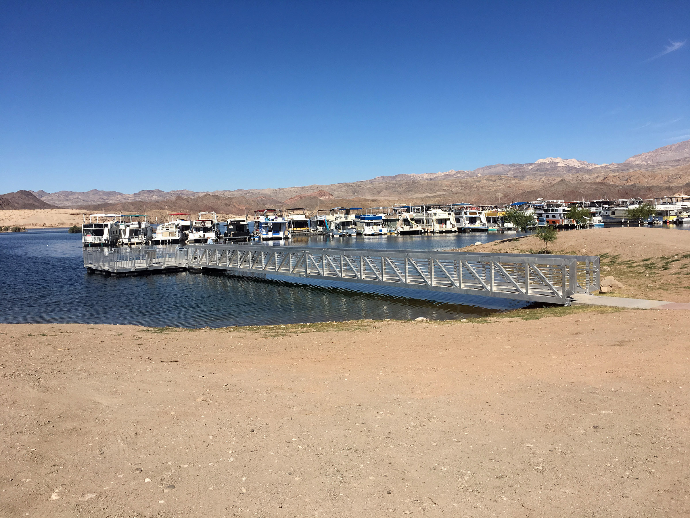Sandy beach leads to accessible fishing pier. Marina is behind with many houseboats moored. Rocky hills are in the background.