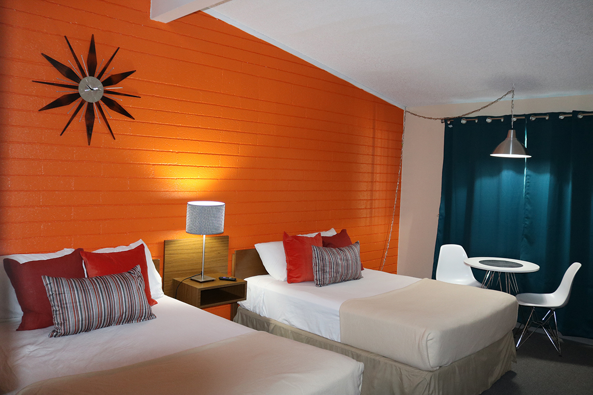 motel room with two beds, table, window and pendant lamp