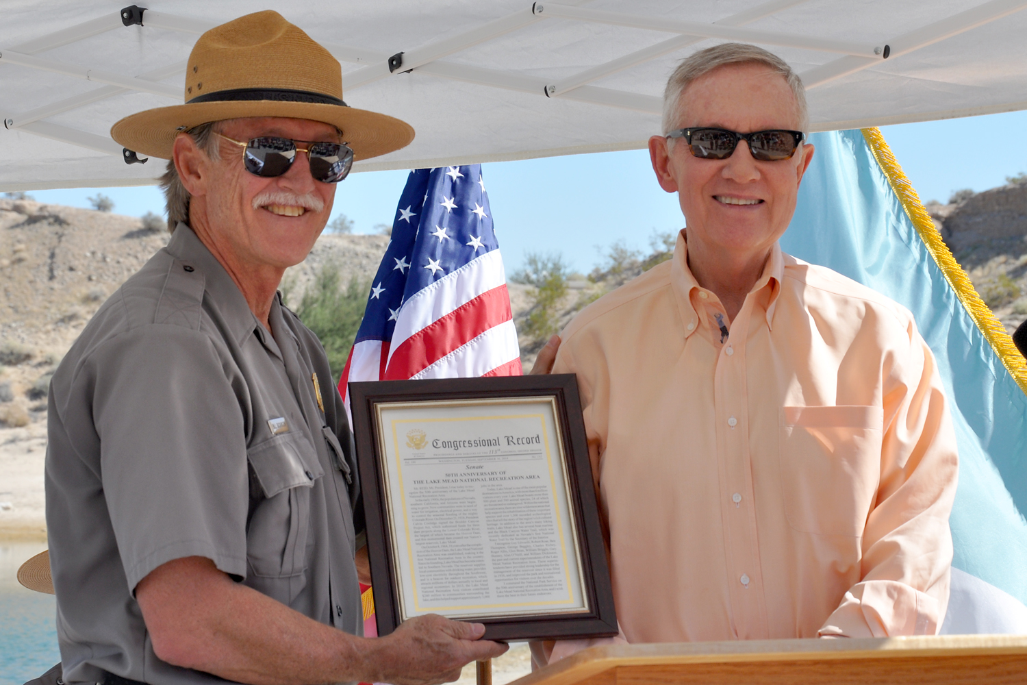 U.S. Sen. Harry Reid presents Superintendent Bill Dickinson with a copy of the Congressional Record that recognized Lake Mead National Recreation Area's 50th anniversary.