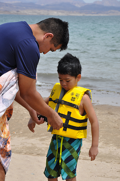Henry Villafana puts a lifejacket on his son, Nicholas, 5, before he goes swimming at Lake Mead. The lifejacket was borrowed from the Lifejacket Loaner Station at Boulder Beach.