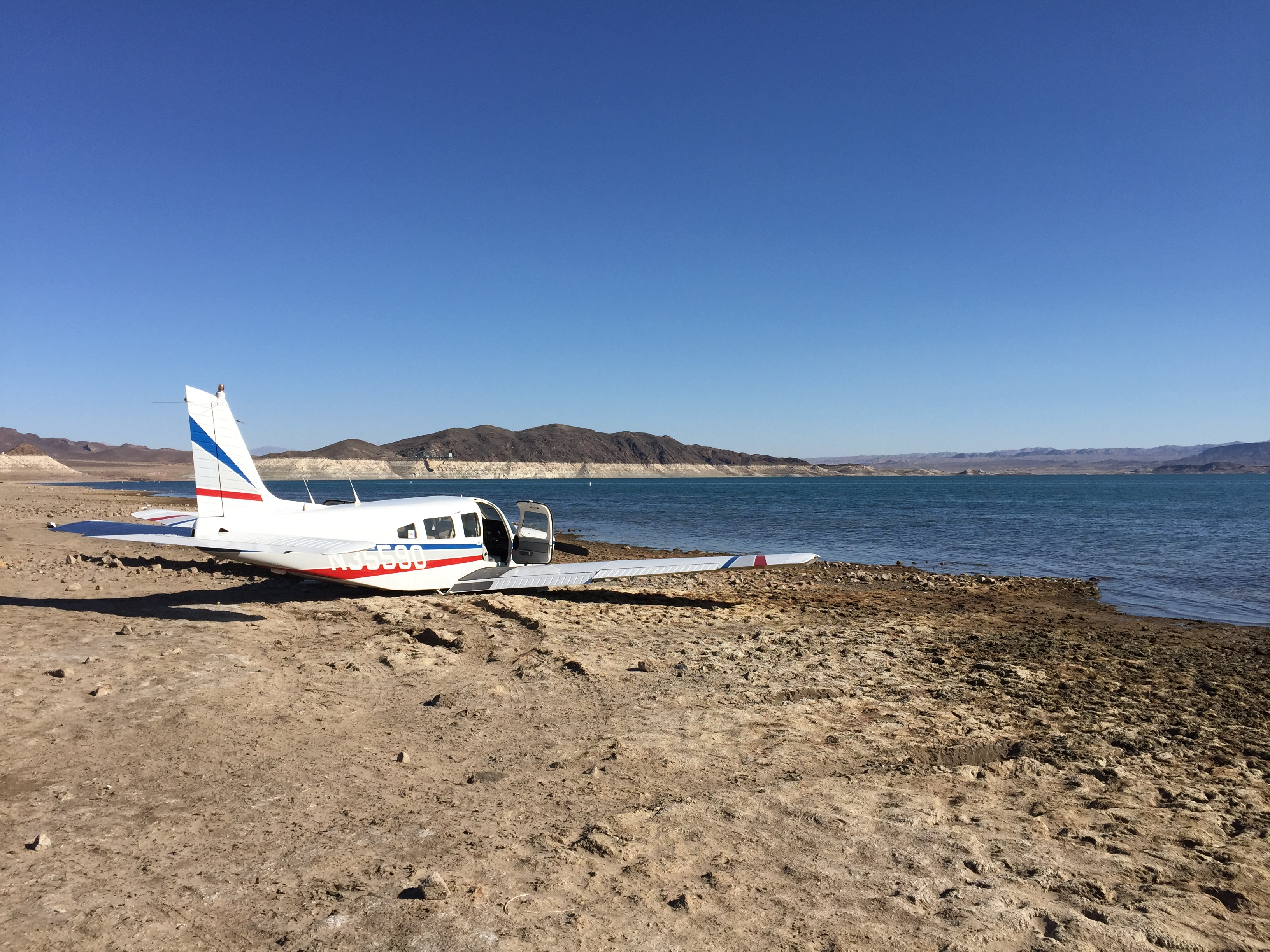 A 1979 Piper PA-32R-301 rests at the water's edge of Lake Mead after a pilot made an emergency landing while flying from North Las Vegas, Nevada, to El Paso, Texas, June 22.