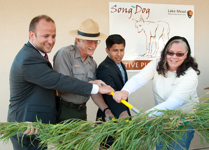 Using a pair of loppers, officials cut a garland made out of native willow branches to signify the grand opening of the Song Dog Native Plant Nursery. Pictured left to right: Matt McKnight, representative from Sen. Harry Reid's office; Bill Dickinson, Lake Mead National Recreation Area superintendent; Jafet Santiago, representative from Sen. Dean Heller's office, Alice Newton, Lake Mead National Recreation Area vegetation manager. (NPS Photo by Andrew J. Cattoir)