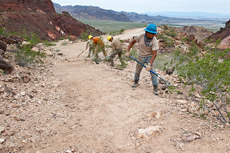 Youth with the Arizona Conservation Corps perform trail work on a spur trail that leads to the Historic Railroad Trail in Lake Mead National Recreation Area. The new trail may be accessed from the Hoover Dam Lodge parking area.