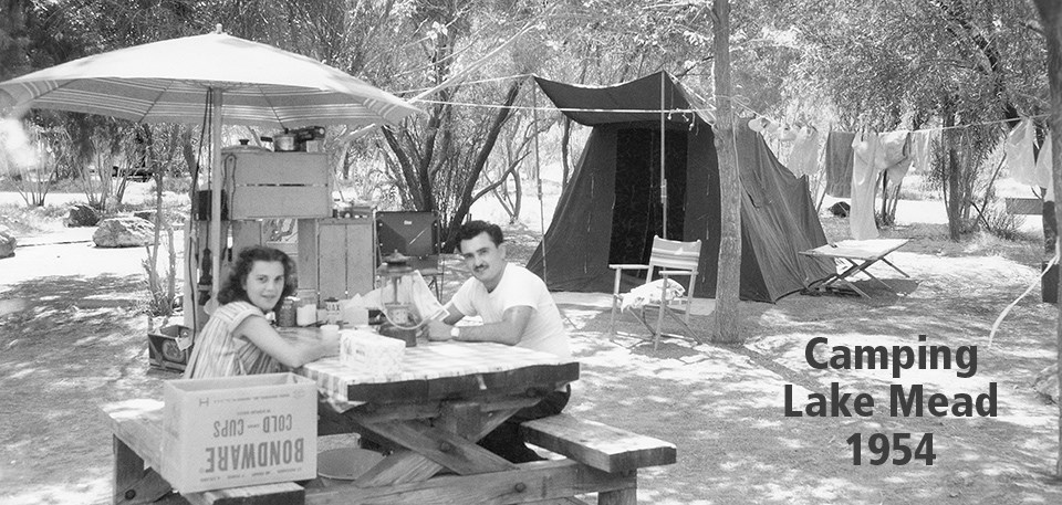 Historic black and white photo of couple sitting at picnic table in campground at Lake Mead in 1954.