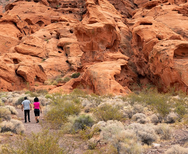 Two hikers walking next to giant red rocks.
