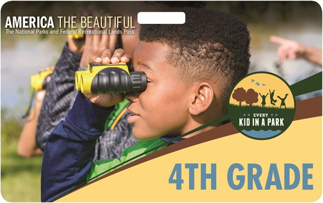 Close up photo of 4th grade boy using binoculars