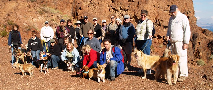 Large group of hikers pose with dogs on trail through red rock walls