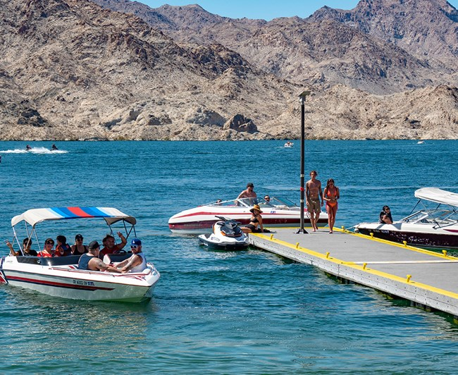 Several boats and water crafts next to a pier with multiple people in swimwear on it.