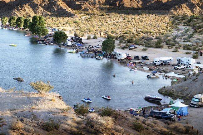 Photo from above water that is surrounded on three sides by boats, personal watercraft and RV's