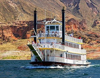 Photo of paddle wheel boat on water with red sandstone formations in background.