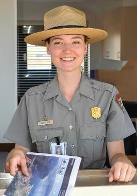 Smiling park ranger holding Lake Mead Newspaper