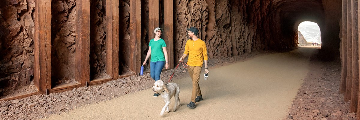 Two hikers with a dog walk through railroad tunnel on Historic Railroad trail