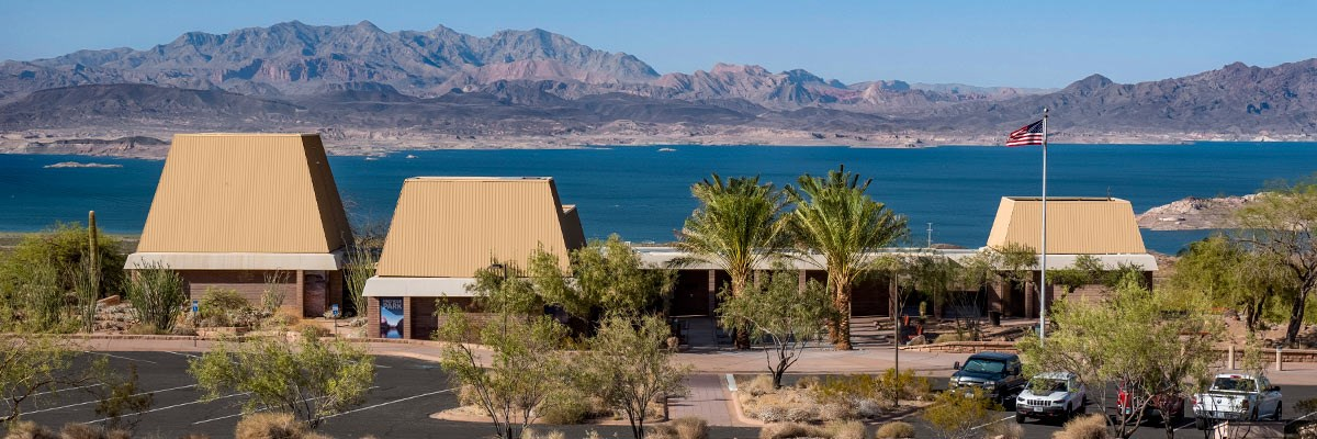 Visitor Center buildings and parking lot with body of water and mountains in background