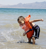 Young child playing in the water while wearing a life jacket
