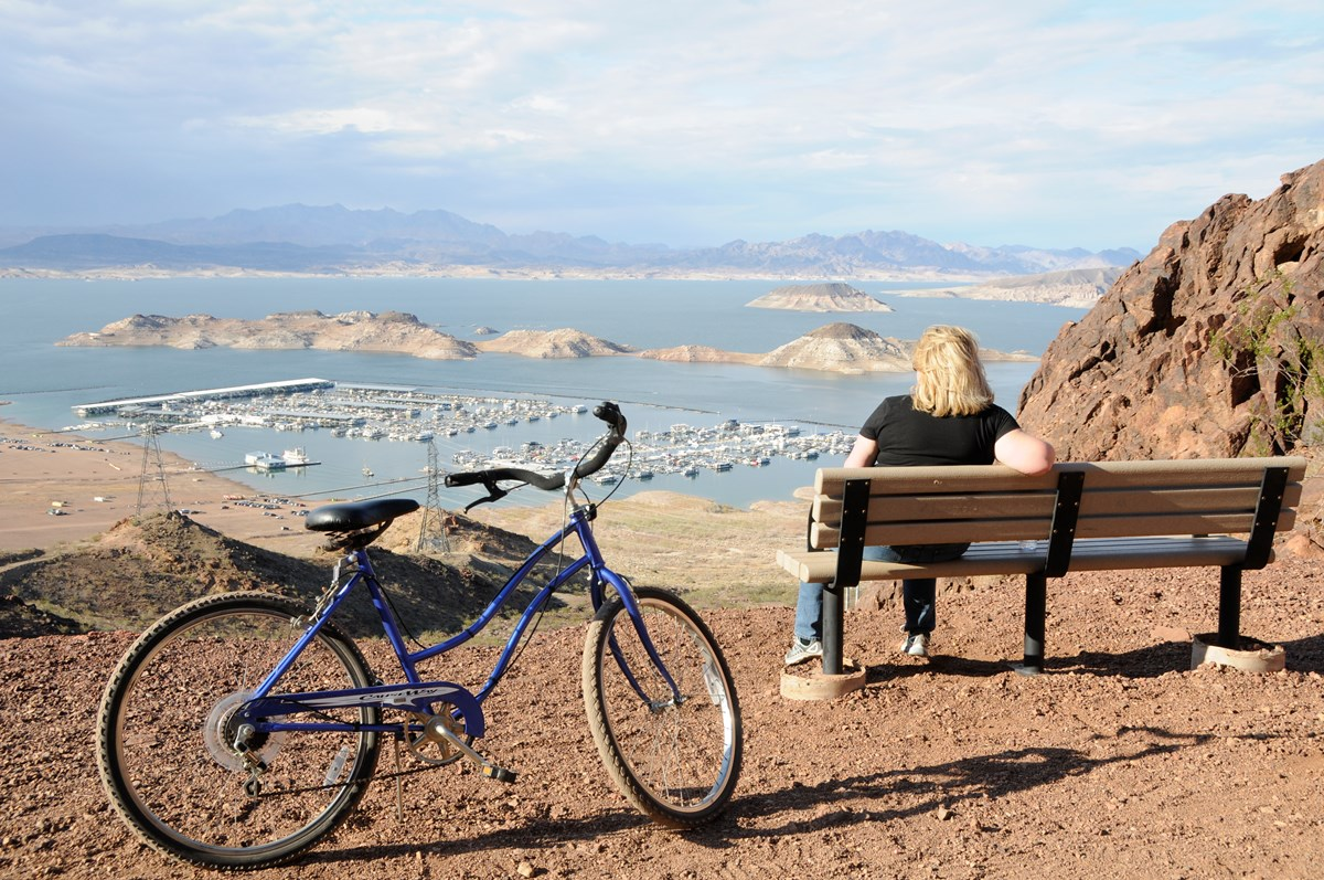 woman sitting on bench by bike looking at lake mead