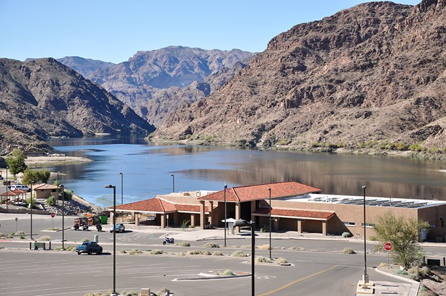 Elevated view of Willow Beach store, launch ramp and parking in foreground. Colorado River surrounded by rugged hills are in the background.