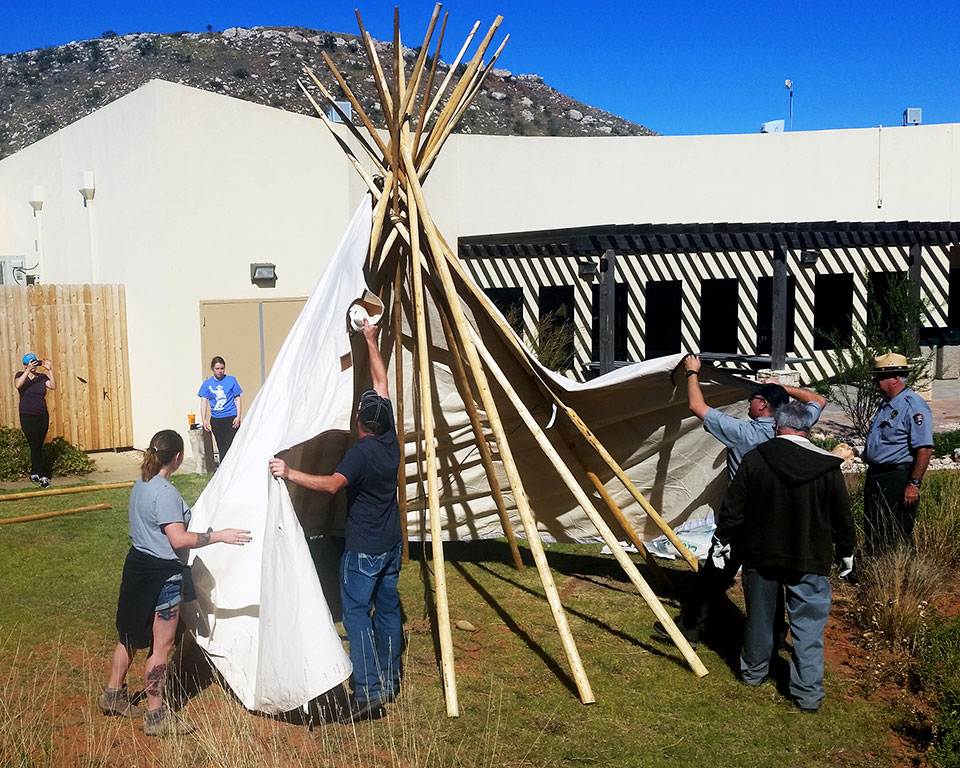 Visitors and Rangers setting up a tepee
