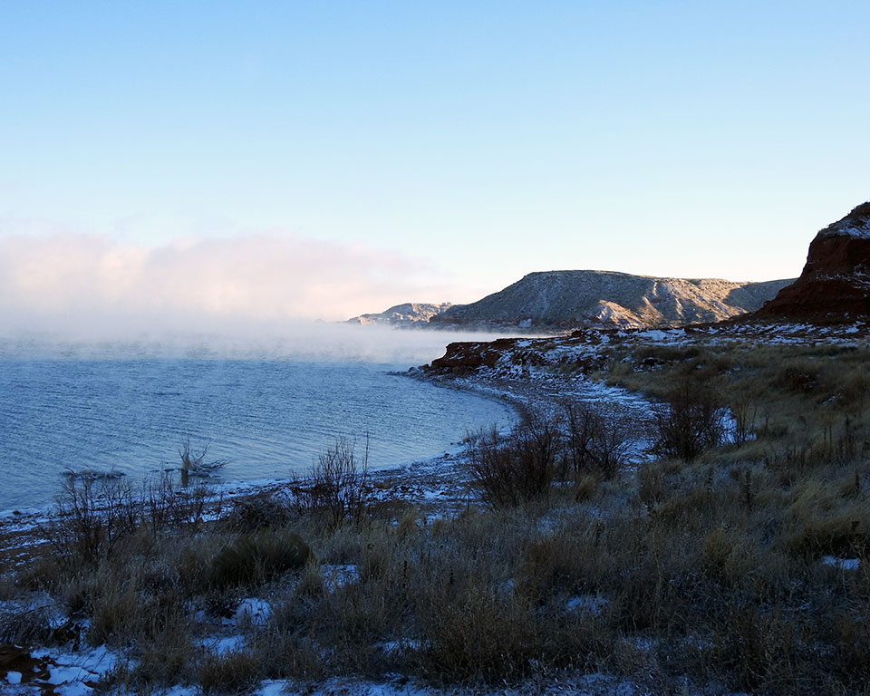 Steam rising from the lake on a snowy morning