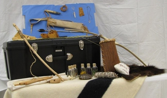 Contents of the trunk are displayed, including bow, furs, twine, arrows, arrowheads, and other small items.