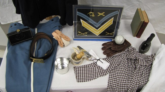 Trunk contents shown, including military uniform jacket and pants, patches, a baseball and glove, a child's smock, and other small items.