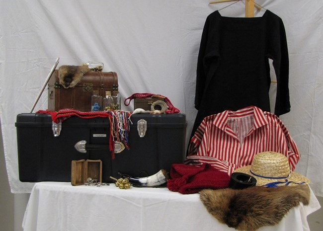 Trunk contents shown, including clothes, a beaver fur, a curved horn, a leather box, bells, and other small items for trading.