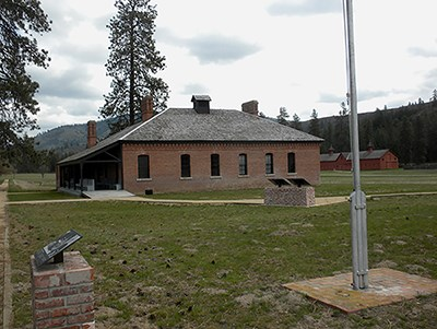 Fort Spokane Visitor Center--a brick building with several windows and 4 chimneys and a flagpole in the foreground.