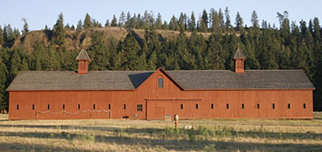 Long red barn with several windows. Black roof and two chimneys. Ponderosa pine covered hillside behind the building.
