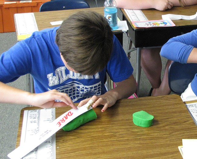 A student uses play dough to make scale models of planets.