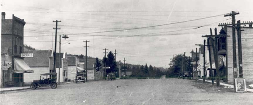 Cars on dirt road with wooden store fronts on either side.