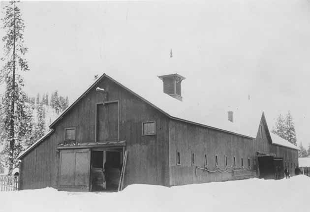 Fort Spokane. Historic photo of quartermaster's barn. Long 2 story barn in snow. Two man at the far end.
