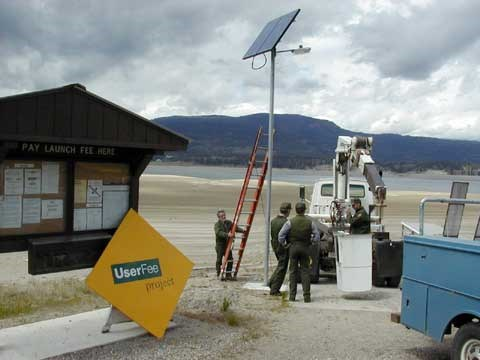 Maintenance installing a solar powered light at a boat dock.