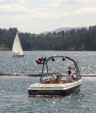 Motor boat on the lake with sailboat in the background.