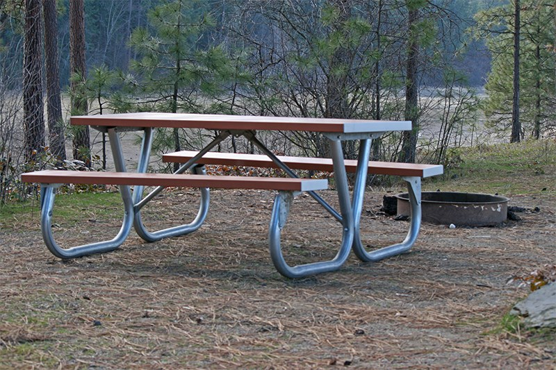 A picnic table and fire pit at a campground