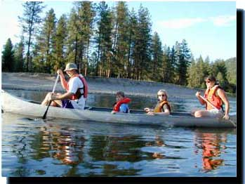 A family canoeing. Parents and two children paddling on the lake.