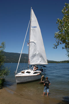 Sailboat loading visitors for a short tour of the lake. White sailboat with sail up.