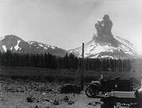 Smoke cloud erupting from a volcano; old car in foreground
