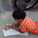 A child laying on the ground works on a Discovery Hunt sheet