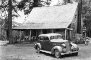 b/w picture of 1935 packard automobile in front of rustic lodge