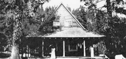 black and white photo showing rustic cabin in the woods with lady and umbrella on porch
